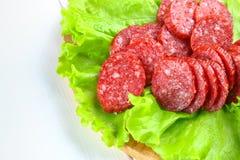 Geräucherte Wurst, Salami hackte in den Scheiben auf einem Salat auf einem hölzernen Kreisschneidebrett auf einer weißen Tabelle Stockfotografie