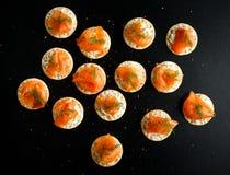 Geräucherter Lachs und weiche chees Canapesaperitifs mit Schnittlauchen auf schwarzer Tabelle Stockfotografie