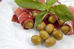Geräucherter Schinken mit Oliven Stockfoto