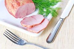 Geräucherter Schinken und Dill auf Platte mit Messer und Gabel stockfotos