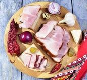Geräucherter Speck, Essiggurken, Zwiebeln, Knoblauch, Paprika auf einem Holztisch - rustikale Art Stockfoto