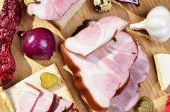 Geräucherter Speck, Essiggurken, Zwiebeln, Knoblauch, Paprika auf einem Holztisch - rustikale Art Stockfotografie