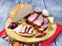 Geräucherter Speck, Essiggurken, Zwiebeln, Knoblauch, Paprika auf einem Holztisch - rustikale Art Lizenzfreies Stockbild