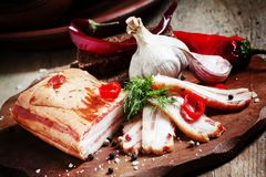 Geräucherter Speck, Knoblauch, roter Pfeffer und Salz auf einem hölzernen Schnittbo Stockbilder