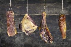 Geräuchertes Fleisch, das am Seil gegen hölzernen Hintergrund mit Rauche hängt lizenzfreie stockfotos