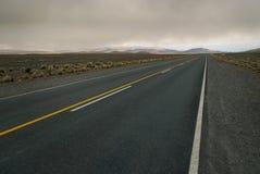 Geräumige bewölkte Landschaft gekreuzt durch leere Straße Lizenzfreie Stockfotografie