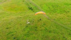 Geräumige Wiese mit einer Person, die das paraplane fliegt Gleitschirm über der Wiese stock footage