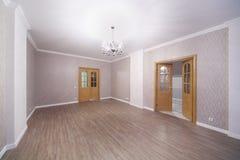 Geräumiger heller Raum mit Bretterboden und geöffneten Türen Lizenzfreies Stockbild