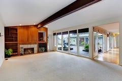 Geräumiges leeres Wohnzimmer mit Kamin und Glaswand Stockfotografie