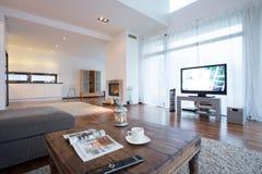 Geräumiges und helles Wohnzimmer mit Fernsehen lizenzfreies stockbild