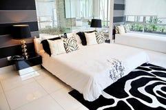 Geräumiges Vorlagenschlafzimmer in einem Kondominium Stockbild