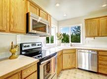 Geräumiges Wohnzimmer mit Kamin, Zweiersofa, Couchtisch und Stuhl Heller Küchenraum Lizenzfreie Stockbilder