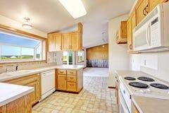 Geräumiges Wohnzimmer mit Kamin, Zweiersofa, Couchtisch und Stuhl Küchenraum mit dem gewölbten ceilign Lizenzfreie Stockfotos