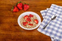 Geröstetes Hafer-Getreide und Erdbeeren auf Tabelle Lizenzfreie Stockfotos