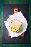 Geröstetes Sandwich mit Salatblättern, -tomaten und -käse mit Gabel auf einem Schneidebrett Stockfotos