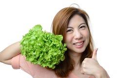 Ger den asiatiska kvinnan för leendet tummen till grönsaken för hydrokulturgräsplaneken Arkivfoton
