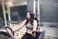 Ger upp den feta kvinnan borrad tröttad förlust för framsidaövningsvikt på pusharmmaskinen genomkörarebegrepp Royaltyfria Bilder