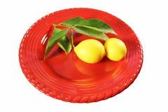 Gerade ausgewählte Zitronen auf roter Platte stockbilder
