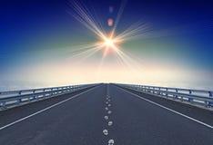Gerade Autobahn mit Abdrücken und ein Leitstern über Horizont stockfotos