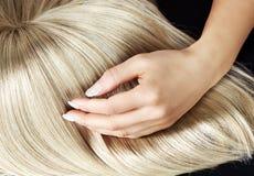Gerade blonde Perücke, die durch eine Frau bürstet Stockbilder