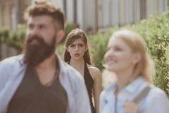Gerade eifersüchtig Eifersüchtiger Frauenblick auf Paare in der Liebe auf Straße Bärtiger Mann, der seine Freundin mit einer ande lizenzfreies stockfoto