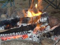 Gerade, entspannend durch das Lagerfeuer, das zu s-` Sitten fertig wird Lizenzfreies Stockfoto