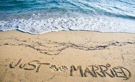 Gerade geheiratet geschrieben in den Sand Stockbilder