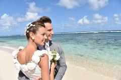 Gerade heiratete Paare, die den schönen karibischen Strand genießen Stockfotos
