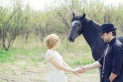 Gerade kleideten verheiratete junge Paare mit Pferd Retro- Lizenzfreie Stockfotos