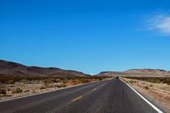 Gerade Landstraße durch ein Wüstengebiet Lizenzfreies Stockbild
