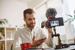 Gerade perfekt! Lächelnder Technologie Blogger, der intelligente Uhrschuhe auf Kamera beim Notieren des neuen Videos für sein Blo stockfoto