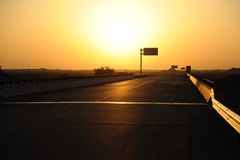 Gerade Straße im Gobi am Sonnenaufgang Lizenzfreies Stockbild