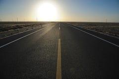 Gerade Straße am Sonnenaufgang Stockfotografie