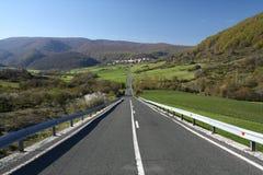 Gerade Straße zu einem Ferndorf - Navarra Stockbild