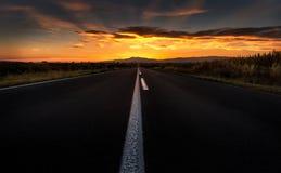 Gerade Straße zum Sonnenuntergang Stockfotos