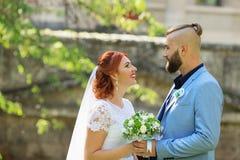 Gerade verheiratete liebevolle Hippie-Paare im Hochzeitskleid und -Anzug herein stockfotografie