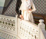 Gerade verheiratete moslemische Paare, die vor Moschee aufwerfen lizenzfreies stockbild