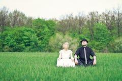 Gerade verheiratete Paare, die im Garten sitzen Lizenzfreies Stockbild