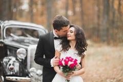 Gerade verheiratetes glückliches Paar im Retro- Auto auf ihrer Hochzeit lizenzfreie stockbilder