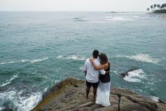 Gerade verheiratetes Paar auf einem trstone umarmt und schaut auf dem Ozeanwasser Stockfoto