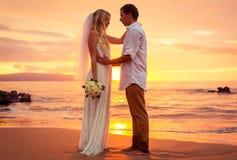 Gerade verheiratetes Paar auf tropischem Strand bei Sonnenuntergang Stockfoto