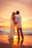 Gerade verheiratetes Paar, das auf tropischem Strand bei Sonnenuntergang küsst Stockbilder