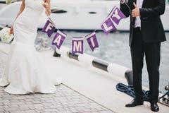 Gerade verheiratetes Paar, das ein FAMILIEN-Zeichen hält Lizenzfreie Stockfotos