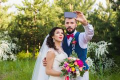 Gerade verheiratetes Paar, das selfie im Park macht stockfotografie