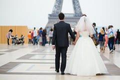 Gerade verheiratetes Paar, das zum Eiffelturm geht Stockfoto