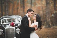 Gerade verheiratetes Paar im Retro- Luxusauto an ihrem Hochzeitstag lizenzfreie stockbilder