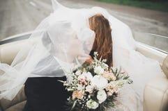 Gerade verheiratetes Paar im Retro- Luxusauto an ihrem Hochzeitstag stockfoto