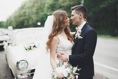 Gerade verheiratetes Paar im Retro- Luxusauto an ihrem Hochzeitstag stockfotos