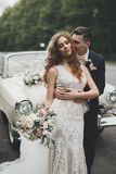 Gerade verheiratetes Paar im Retro- Luxusauto an ihrem Hochzeitstag lizenzfreie stockfotografie