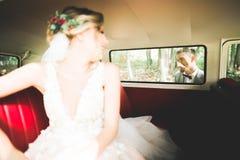 Gerade verheiratetes Paar im Retro- Luxusauto an ihrem Hochzeitstag lizenzfreie stockfotos